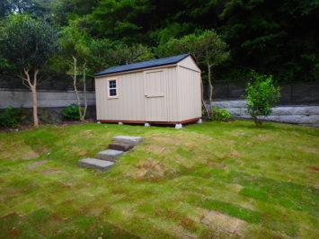 彩葉苑が策定した小屋のある芝庭とスッキリした雑木のアプローチのある庭。